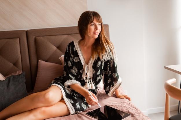 Kobieta za pomocą tabletu i chłodzenie w łóżku