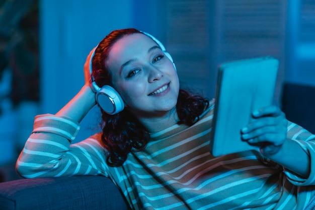 Kobieta za pomocą tabletu i słuchawek w domu na kanapie