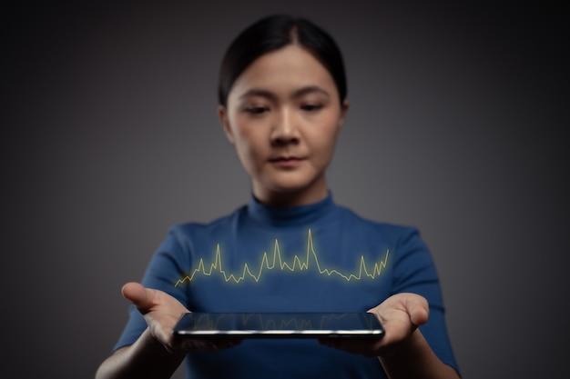Kobieta za pomocą tabletu planowania marketingu cyfrowego z efektem hologramu wykresu