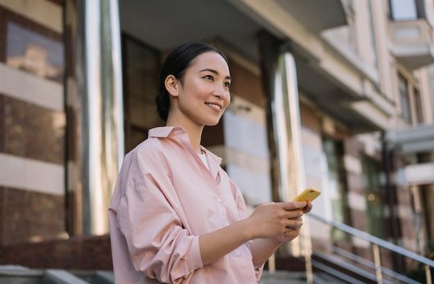 Kobieta za pomocą telefonu komórkowego, komunikacji, czekając na taksówkę na zewnątrz