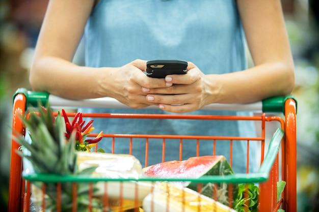 Kobieta za pomocą telefonu komórkowego podczas zakupów w supermarkecie.