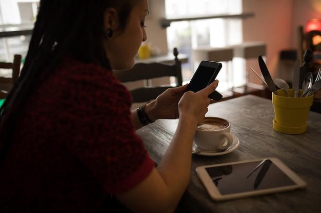 Kobieta za pomocą telefonu komórkowego w kawiarni