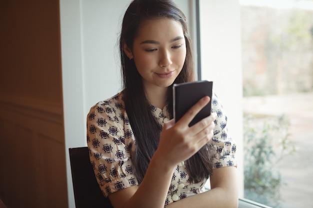 Kobieta za pomocą telefonu komórkowego w pobliżu okna
