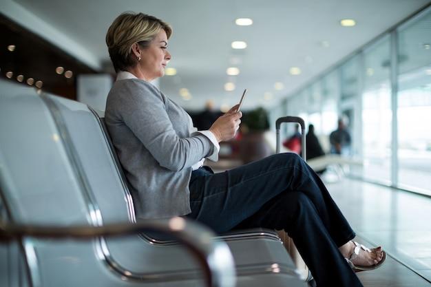 Kobieta za pomocą telefonu komórkowego w poczekalni