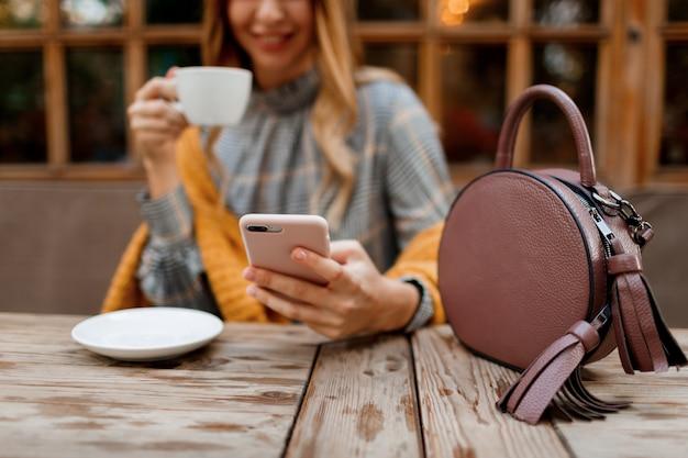 Kobieta za pomocą telefonu komórkowego, wiadomości sms i picia kawy. stylowa torba na stół. ubrana w szarą sukienkę i pomarańczową kratę. przyjemny poranek w kawiarni.