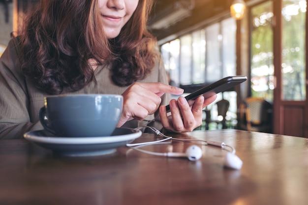 Kobieta za pomocą telefonu komórkowego ze słuchawkami i filiżanką kawy na drewnianym stole w kawiarni