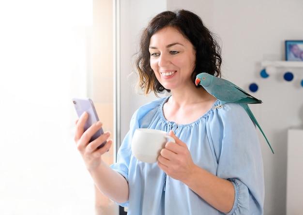 Kobieta za pomocą telefonu z filiżanką papugi i kawy.
