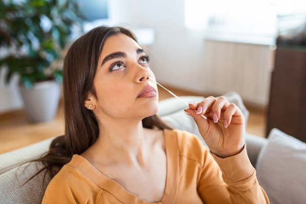 Kobieta za pomocą wacika podczas wykonywania testu pcr na koronawirusa w domu. kobieta za pomocą szybkiego testu diagnostycznego na koronawirusa. młoda kobieta w domu używa wymazu z nosa na covid-19.