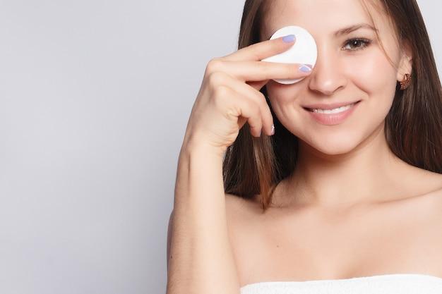 Kobieta za pomocą wacika. szczęśliwy uśmiechający się piękna młoda kobieta czyszczenia skóry przez wacik. jasne tło. piękna kobieta spa uśmiecha. doskonała świeża skóra. koncepcja pielęgnacji skóry i młodzieży