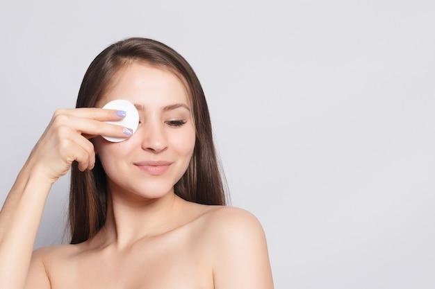 Kobieta za pomocą wacika. szczęśliwy uśmiechający się piękna młoda kobieta czyszczenia skóry wacikiem. jasne tło. piękna kobieta spa uśmiechając się. idealna świeża skóra. koncepcja pielęgnacji młodości i skóry
