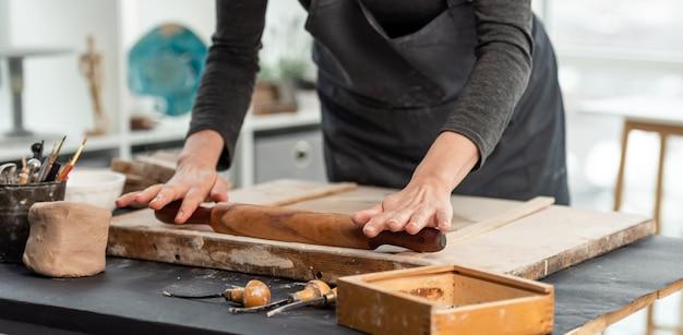 Kobieta za pomocą wałka do ciasta na glinie w warsztacie ceramiki