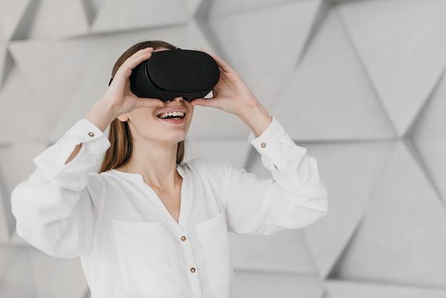 Kobieta za pomocą widoku z boku zestawu słuchawkowego wirtualnej rzeczywistości