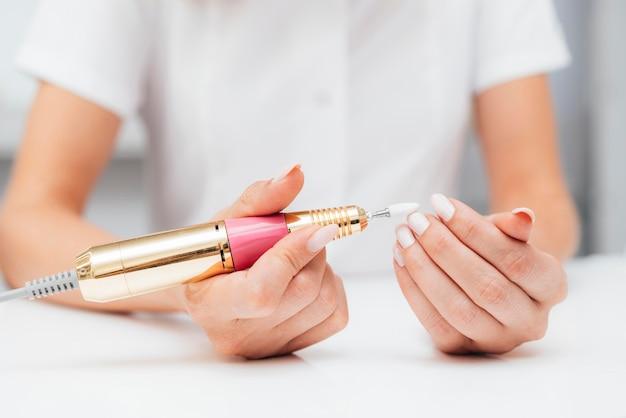 Kobieta za pomocą widoku z przodu cyfrowego pilnika do paznokci