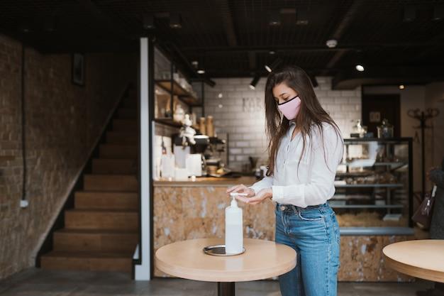 Kobieta za pomocą żelu dezynfekującego czyści ręce wirusa koronawirusa w kawiarni.