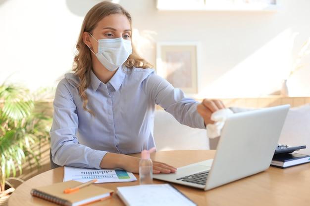Kobieta za pomocą żelu do dezynfekcji rąk. czyszczenie laptopa za pomocą środka dezynfekującego. koronawirus ochrona.