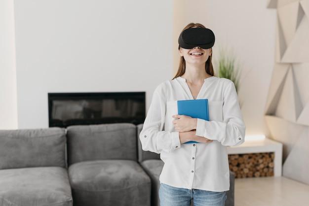 Kobieta za pomocą zestawu słuchawkowego wirtualnej rzeczywistości i trzymając książkę