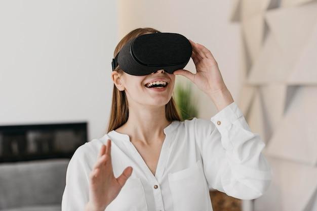 Kobieta za pomocą zestawu słuchawkowego wirtualnej rzeczywistości i uśmiecha się