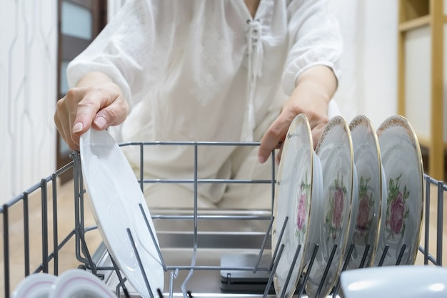 Kobieta za pomocą zmywarki do naczyń, z bliska