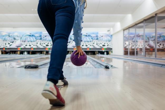 Kobieta zabawy grając w kręgle w klubie rzucanie piłki