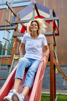 Kobieta zabawy na slajdzie dla dzieci. dzieciństwo nie kończy całego życia, dorośli jako dzieci. koncepcja stylu życia.