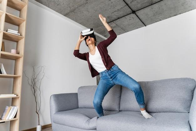 Kobieta, zabawy w domu z zestawem słuchawkowym wirtualnej rzeczywistości