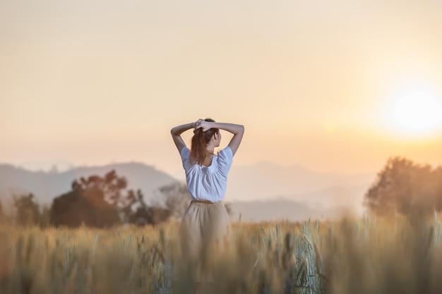 Kobieta zabawy w polu jęczmienia o zachodzie słońca