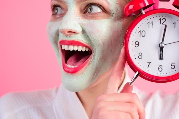 Kobieta zabiegów kosmetycznych spa z maską kosmetyczną na twarzy trzyma zegar wellness i koncepcję spa twarzy