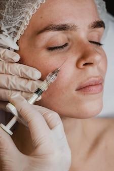 Kobieta zaczyna zabieg upiększający na twarz w centrum odnowy biologicznej
