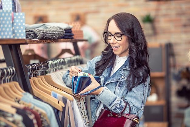 Kobieta zadowolona z zawartości swojego portfela wybiera ubrania do kupienia w sklepie odzieżowym.