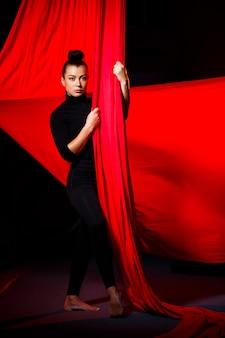 Kobieta zajmuje się akrobacjami powietrznymi na ciemnym tle. gimnastyczka sportowa wykonująca ćwiczenia na płótnie