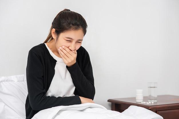 Kobieta zakaszlała, zakryła usta dłonią i usiadła na łóżku.