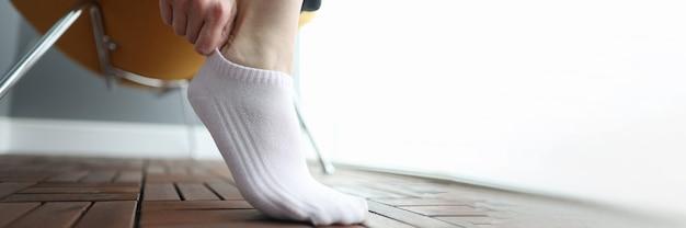 Kobieta zakłada białą krótką skarpetkę na nogę