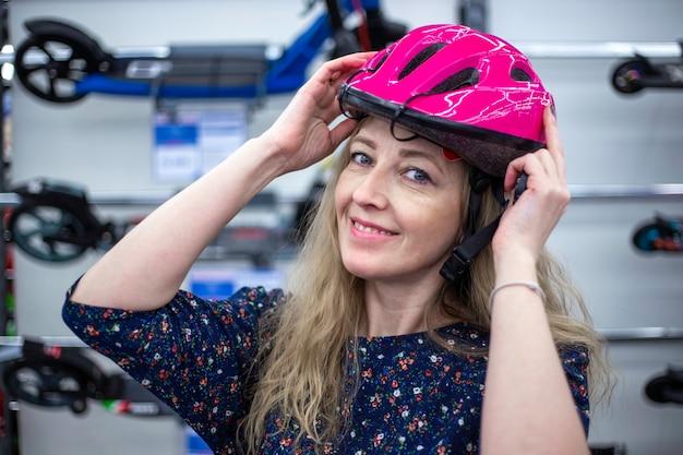 Kobieta zakłada kask rowerowy i uśmiecha się. zakupy w sklepie