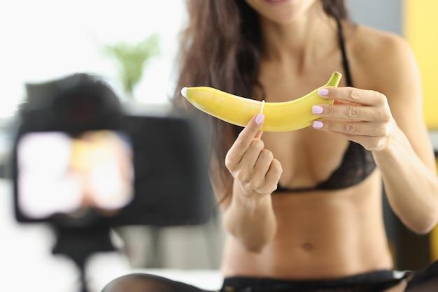 Kobieta zakłada prezerwatywę na banana i rejestruje go w aparacie
