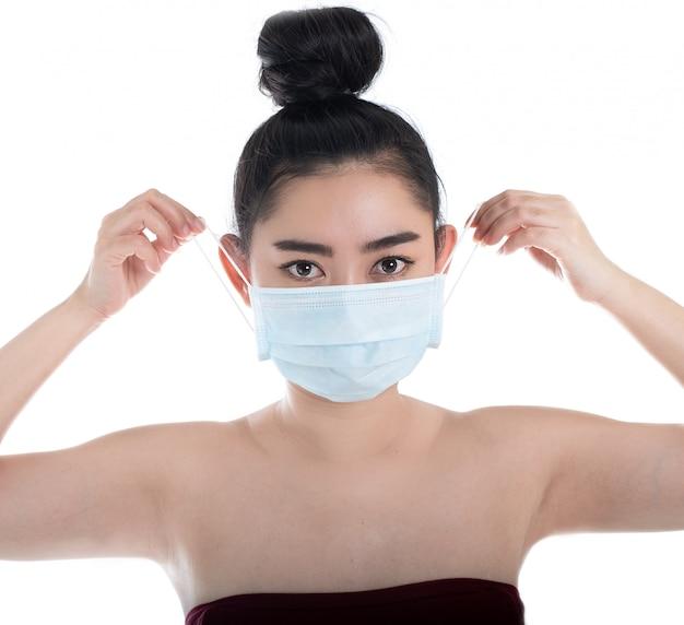 Kobieta zakładająca maskę medyczną w celu ochrony przed unoszącymi się w powietrzu chorobami układu oddechowego
