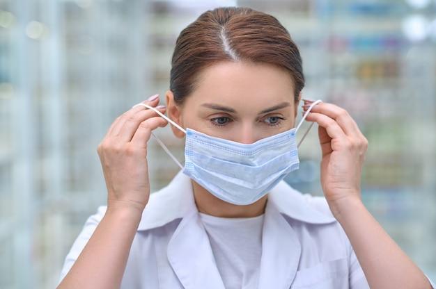 Kobieta zakładająca maskę ochronną w aptece