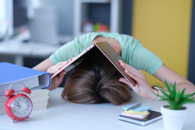 Kobieta zakryła głowę laptopem i położyła go na stole w miejscu pracy. koncepcja opracowania godzin pracy