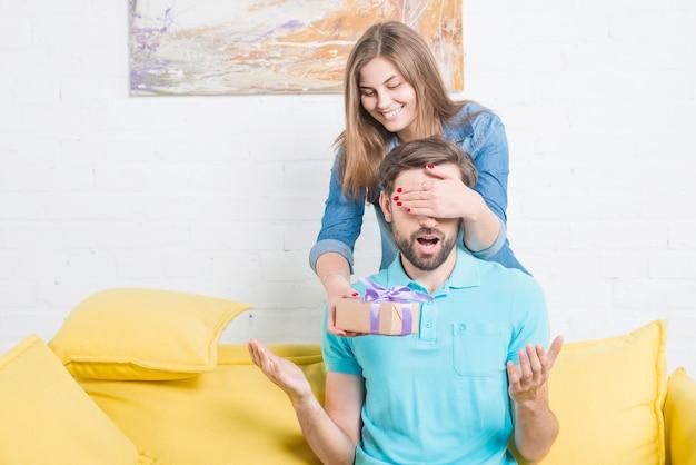 Kobieta zakrywa jej chłopaka oczy daje on valentine prezentowi