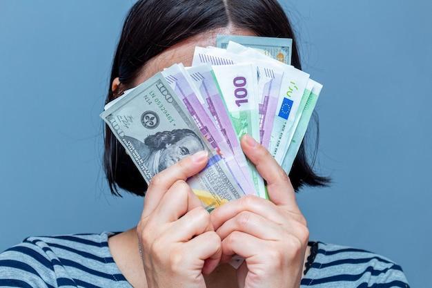 Kobieta zakrywa twarz banknotami na szarym tle