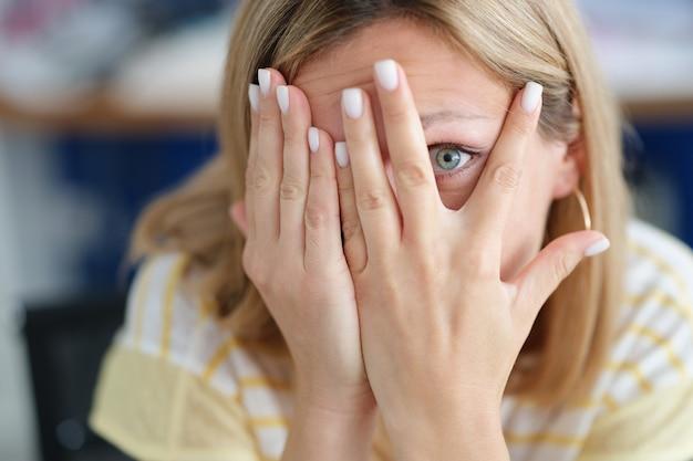 Kobieta zakrywa twarz dłonią patrząc przez palce wyrazy emocji i cierpienia