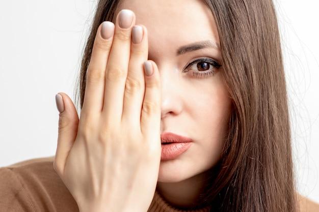 Kobieta zakrywa twarz ręką