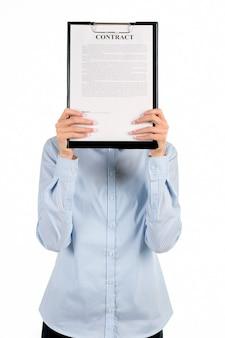 Kobieta zakrywa twarz schowkiem. twarz bizneswoman zakryta schowkiem. skoncentruj się i przyjrzyj się uważnie. to ktoś za tym stoi.