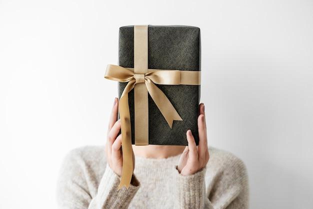 Kobieta zakrywa twarz szarym prezentem