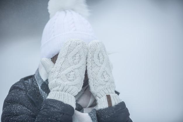 Kobieta zakrywa twarz w białych rękawiczkach z dzianiny w śnieżny dzień na zewnątrz.