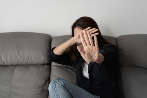 Kobieta zakrywa twarz w obawie przed przemocą domową, pojęcie przemocą i znęcaniem się.