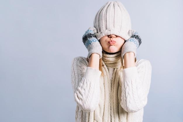 Kobieta zakrywa twarz z nakrętką i dmuchającymi policzkami
