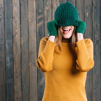 Kobieta zakrywa twarz z nakrętką