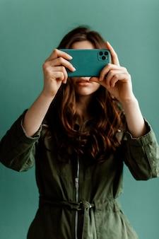 Kobieta zakrywająca twarz smartfonem