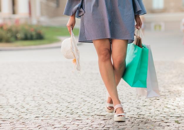 Kobieta zakupoholiczka z potrójnymi nogami z papierowymi torbami na zakupy spacery po mieście. przyciąć zdjęcie