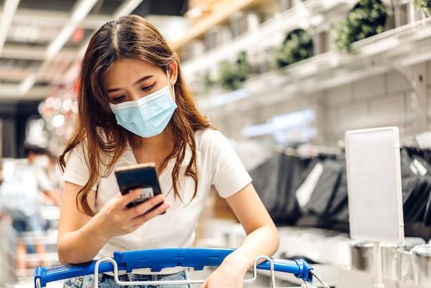 Kobieta zakupy i używać smartfona w sklepie